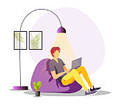 Young man working or studying at home in a beanbag chair. Home office online freelancer working job at home, E-learning and chatting concept.