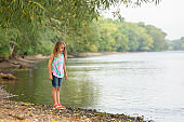 Young Girl Standing on Bank of Mississippi River in Summer