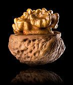 Macro photo of half opened walnut with kernel isolated on a black background