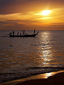 silhouette unidentified local fisherman go fishing by small traditional long tail boat in evening time with sunset