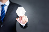 Businessman touching an hexagonal button on a digital interface. Concept about technology and choices