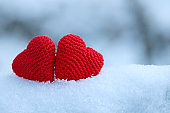 Love hearts, Valentine's card, two red knitted symbols of passion in the snow drift