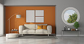 Modern living room with round window on gray wall