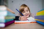 Smiling boy writing homework at home