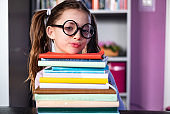 Portrait small cute girl and bunch of books at home