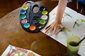 Child is doing handprints whit watercolors