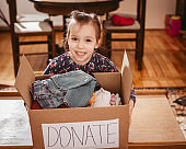 Donation concept. Kid holding donate box with clothes