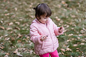 Child holds acorns in her hand in the park