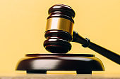 Judge Gavel on a wooden table and yellow-orange background. The concept of law. sentence, justice