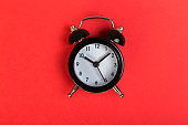 black vintage alarm clock on a red background, top view. concept of time, daily routine