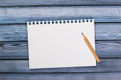 top view of blank open notebook paper on wooden background, office equipment, school stationary and education concept