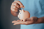 male hands put a coin in a pink piggy bank. Concept of saving money or savings, investment