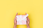 Hands holding craft paper gift box with a gift for Christmas, New Year, Valentine's Day or anniversary on a yellow background, top view