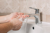 Hygiene concept. Washing hands with soap under the tap with water. handsome male hands and water in the bathroom.