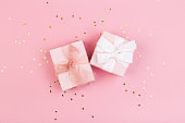 Gift or gift box and stars confetti on a pink table from above. Flat composition for birthday, mothers day or wedding.