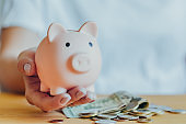 woman's hand hold a pink piggy bank on the table. Concept of saving money or savings, investment during the global crisis