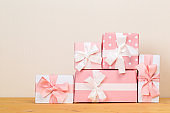 gift boxes on a wooden table. colorfully wrapped gifts with pink ribbons. Holiday Greeting Card.