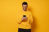 Young handsome man exchanging text messages with friends via smart phone, having fun, wearing bright sweatshirt, isolated on yellow background