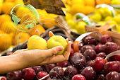 Woman hand choosing prunes at supermarket. Concept of healthy food, bio, vegetarian, diet.