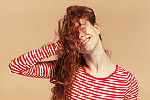 Close-up portrait of redhead teen girl pressing loose curly hair to her head, creating messy hairstyle, looking extremely happy, having fun with closed eyes, isolated on brown background