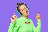 Close-up portrait of young positive girl laughing, singing and dancing while listening to music in blue wireless headphones, isolated on purple background