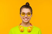 Close-up portrait of young smiling girl dressed in neon green top, wearing colored glasses and wireless headphones around neck, isolated on yellow background