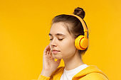 Close-up portrait of young teenage girl listening to music through wireless headphones, keeping eyes closed to concentrate on sound, isolated on yellow background