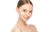 Beauty portrait of young beautiful woman with face cream on cheek, isolated on white background