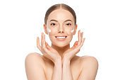 Young happy beautiful smiling woman with drops of cream on cheeks, holding palms close to face, isolated, white background. Female skincare concept