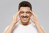 Young male experiencing severe headache, pressing fingers to temples, keeping eyes closed trying to ease pain, feeling sick and troubled, isolated on gray background
