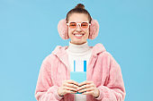 Young happy female holding passport with tickets, ready to go travelling in winter, isolated on blue background. Christmas tour or journey and tourism concept