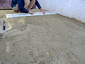 A man smoothes a construction site with a screed tool for laying paving slabs