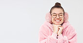 Horizontal banner of young smiling girl wearing pink furry coat, earmuffs and glasses, smiling with eyes closed, making wish, isolated on gray background, copy space on left