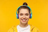 Young smiling teenage girl wearing t-shirt, hoodie and blue wireless headphones, listening to favorite music and relaxing, isolated on yellow background
