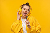 Trendy girl singing favorite song out loud in phone as mic, wearing wireless headphones, isolated on yellow background. Karaoke online app.