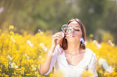 beautiful woman blowing soap bubbles