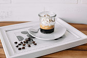 Coffee with ice cream in glass, coffee beans on photography frame, affogato