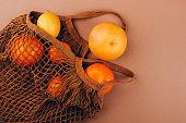 Fresh fruits in a mesh bag, top view.