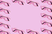 Many reading glasses on pink background pattern