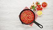 Cooking homemade spaghetti with tomato sauce in cast iron pan served with red chili pepper, fresh basil on white wooden background.
