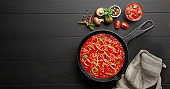 Cooking homemade spaghetti with tomato sauce in cast iron pan served with red chili pepper, fresh basil over black rustic wooden background.