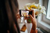 Woman photographing her arrangement