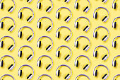 Wireless green headphones on an yellow background