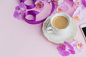 Delicate flatlay composition with morning cup of coffee with milk or cappuccino, phone and purple orchid flowers on light pink background.