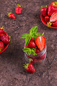 Heap of fresh strawberries and mint leaves in glass jar on dark brown background. Healthy eating and diet food concept.