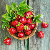 Heap of fresh strawberries in a basket bowl on rustic wooden background. Healthy eating and diet food concept.