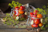 Preserving fresh and pickled tomatoes, seasonings and garlic on wooden table. Healthy fermented food. Home canned vegetables.