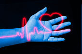 a human hand reaches out and hold a red heart rate graphic with black background
