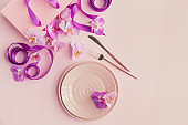 Flower and table settings overhead composition on light pink background. Pink ceramic plates, cutlery, pink gift bag with purple ribbons and pink orchid flowers. Holiday modern table decoration