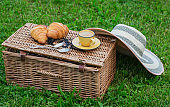 Wicker picnic basket on grass with food and coffee